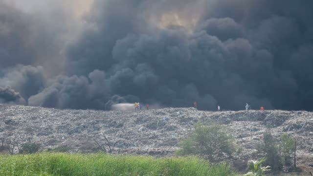 Firefighter and Burning garbage heap of smoke