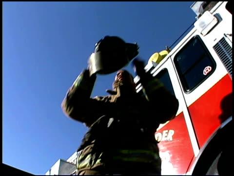 Firefighter putting on helmet