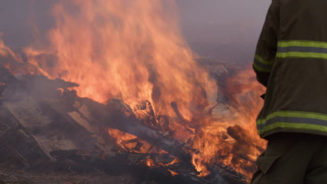 A firefighter sprays water on flames burning above a pile of rubble in the wake of a house fire