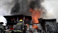 Firefighters battled on Friday to put out a raging fire that has engulfed an informal settlers area beside a river in Manila