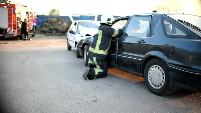 Firefighters helping car accident victim