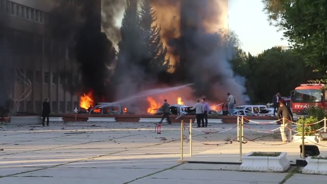 Firefighters try to extinguish a fire at the site of an explosion in the parking lot of the governor's office in southern Turkey's Adana province...