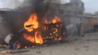 Firefighters try to extinguish the fire after a bomb placed under the car of a Syrian opposition security official blasted in northern Idlib city of...