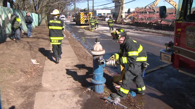 Fireman connects hose to a hydrant as the crew works to contain a fire in Maplewood NJ