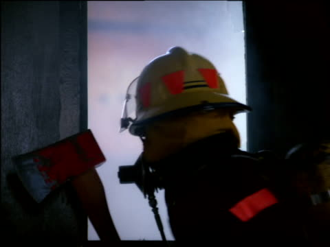 Fireman holding axe peers through broken window checking room beyond for danger