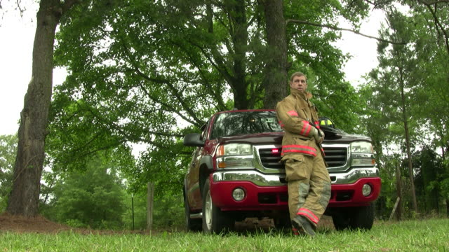 Fireman rests by leaning on his truck