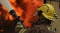 Fireman using hose on flames inside a burning house