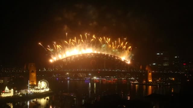 Fireworks explode over the Sydney Harbour Bridge and the Sydney Opera House during the fireworks display on New Year's Eve on January 1 2015 in...