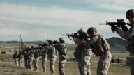 Firing line of soldiers practicing shooting form.