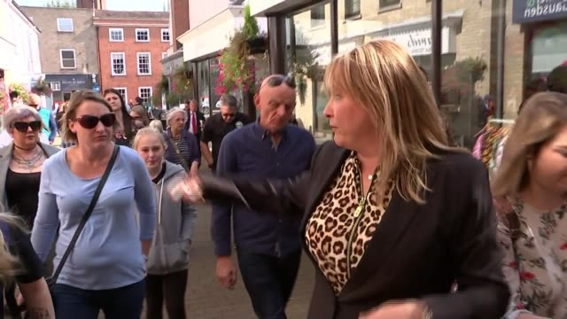First anniversary of the disappearance of Corrie McKeague Nicola Urquhart leading group along street and talking to group of people and cameras as...