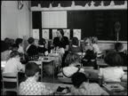 WS first grade classroom in 1954 teacher leads a group of students in a discussion / MS students seated with textbooks behind them a girl paints on a...