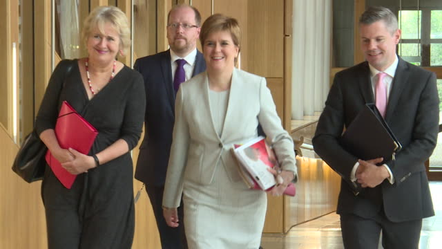 First Minister Nicola Sturgeon and associates including Roseanna Cunningham MSP and Derek Mackay MSP walk through the halls of Holyrood as she...
