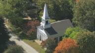 AERIAL First Parish Church amongst autumn foliage / Lincoln, Massachusetts, United States