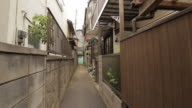 First person view of a walk in a quiet residential district Entering a narrow alley in a corner and walk through to the other end