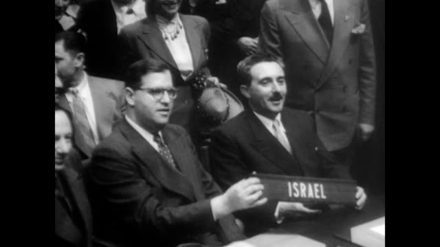 / First president of Israel Chaim Azriel Weizmann and his wife Vera Weizmann walk down street in Tel Aviv waving to gathered crowd / inside the...