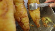 Fish fillets being battered and fried in a deep fryer at a fish and chip shop