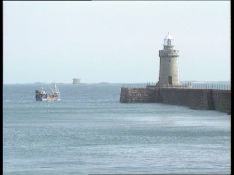 Fish war NAT CHANNEL IS Guernsey St Peter Port AIRV Port LS Fishing boat out to sea past small lighthouse INT/BOAT CBV Crewman at ship's wheel as...