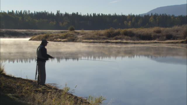 ZO WS Fisherman casting line into mountain lake / Grand Teton National Park, Wyoming, USA