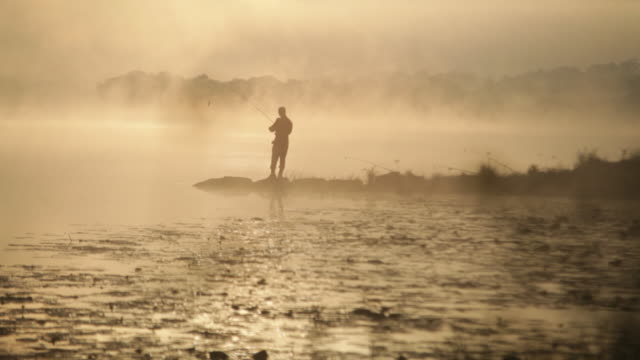 A Fisherman casting on a river bank in the misty morning