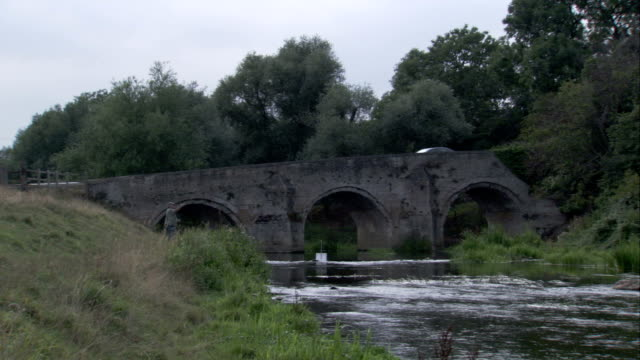 A fisherman casts into a stream flowing under an arched bridge. Available in HD.