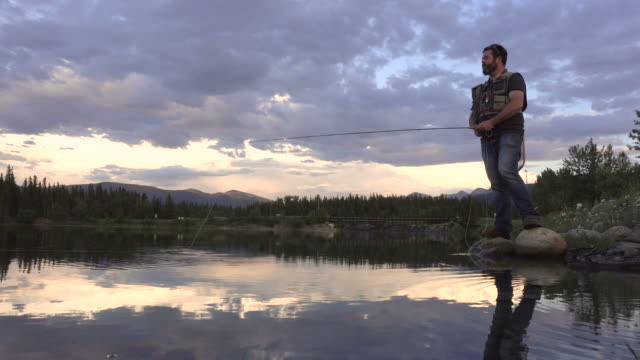 Fisherman casts line into lake with mountains in the distance