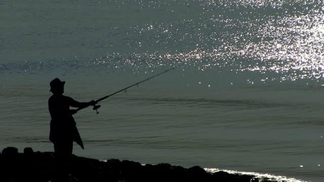 Fisherman fishing at bay
