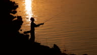 fisherman fishing at sunset.