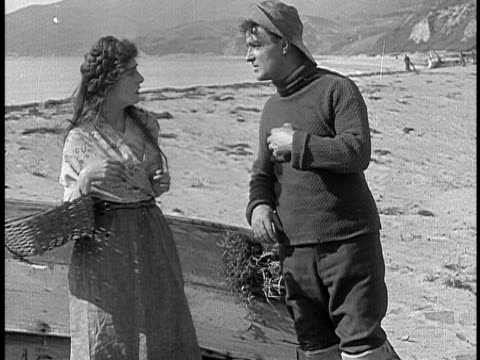 1911 B&W Fisherman flirting with flower girl on beach, asking her to go with him/ Santa Monica, California, USA