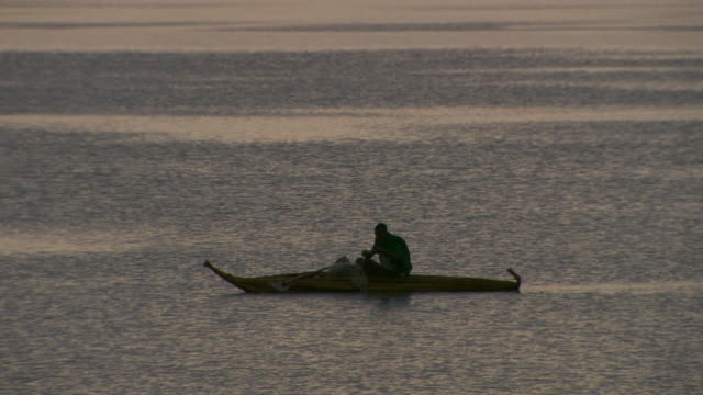 A fisherman in a papyrus boat lays his nets into Lake Tana.