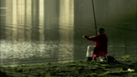 A fisherman lowers his fishing pole into the River Arno, Florence. Available in HD.
