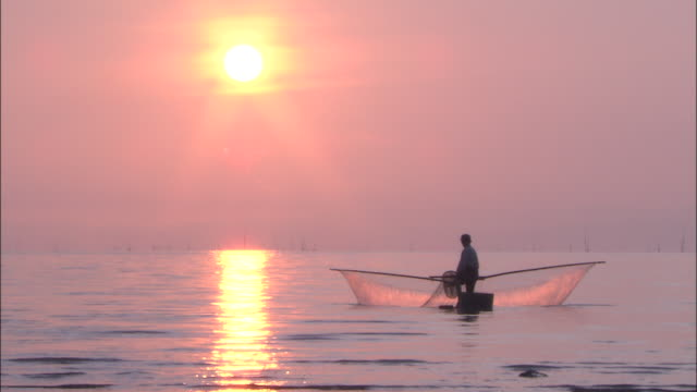 Fisherman net fishing at dawn