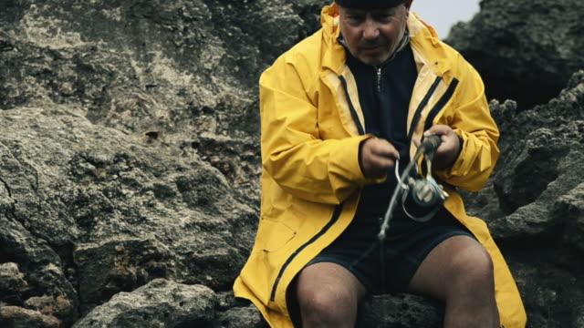 Pescatore sulla costa rocciosa