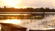 Fiskare på longtail båt i solnedgång