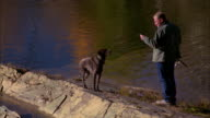 A fisherman readies his fishing pole while his dog watches. Available in HD.
