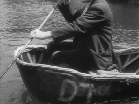 A fisherman rocks and turns a coracle to show its stability while in the water
