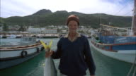 Fisherman standing in harbour holding up large yellowtail fish, South Africa Available in HD.