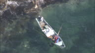 A fishermen in the Sea of Japan lifts fish into his motorboat on the coast of the Shakotan Peninsula.