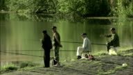 Fishermen sit on stools on a riverbank waiting for a bite. Available in HD.