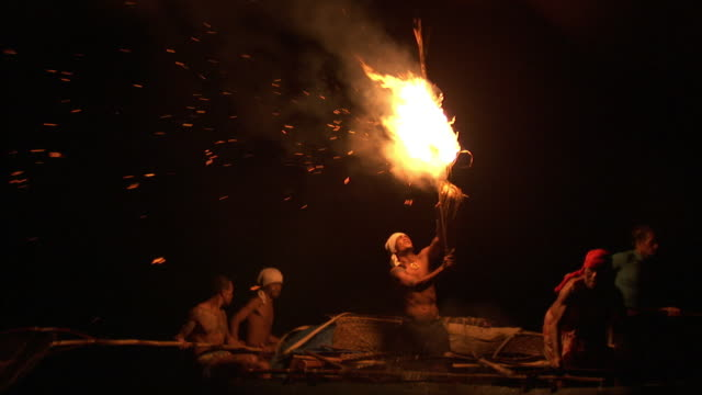 Fishermen use flaming torch to attract fish at night, Solomon Islands