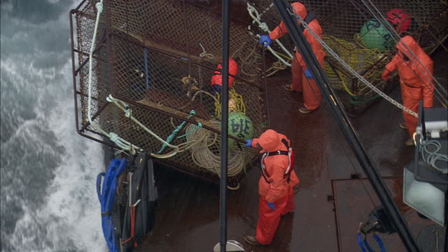 Fishermen wearing raincoats work on the deck of a fishing boat during a storm.