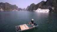 WS Fisherwoman in Ha Long Bay with passenger ship in background / Vietnam