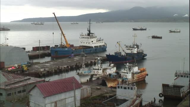 A fishing boat glides against a pier at Yuzhno-Kurilsk port on Kunashiri Island.