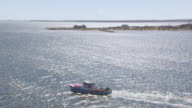 WS AERIAL POV Fishing boat moving in sea with town in background / New Bedford, Massachusetts, United States
