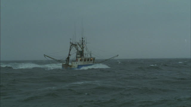 A fishing boat sails across a choppy ocean.
