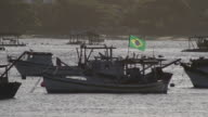 Fishing boats floating in the sea in the late afternoon with the flag of Brazil NO