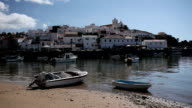 WS Fishing boats moored in harbor, townscape in background / Ferragudo, Algarve, Portugal