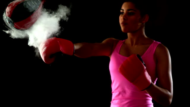 Fit woman in pink punching speed bag