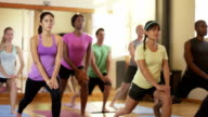 Fitness class with multiethnic students doing Yoga and warming up