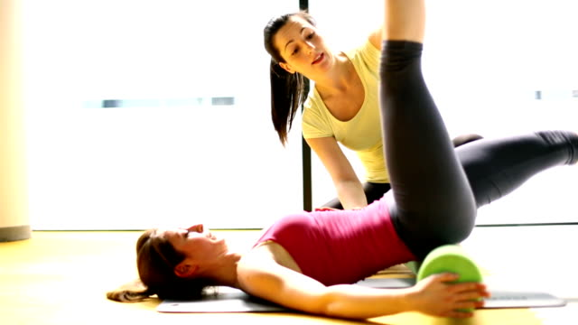 Fitness instructor exercising with a client.