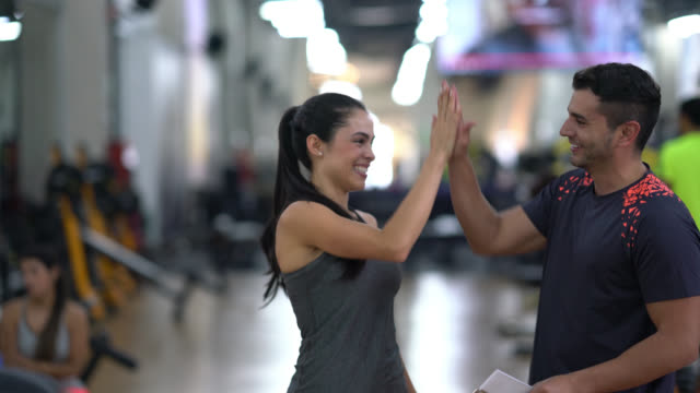 Fitness instructor giving a high five to his customer